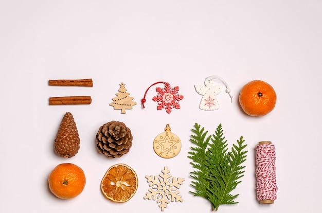 Witte kerst- of nieuwjaarsoppervlak met jeneverbessentak, kaneel, anijs, geschenkdoos, droge sinaasappels, houten speelgoed, karamel kerstsnoepjes, dennenappels, noten
