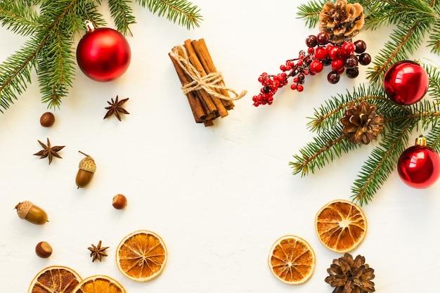 Witte kerstachtergrond met een platte lay-out van stukjes sinaasappel, anijssterren, kaneel, noten, sparrentak en rode bessen. bovenaanzicht.