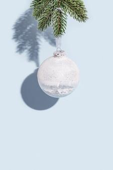 Witte kerstbal opknoping op pijnboomtak