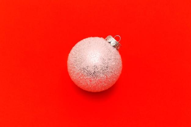 Witte kerstballen op een rode achtergrond met ruimte voor tekst