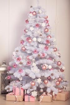 Witte kerstboom en geschenken. gezellig nieuwjaar interieur.