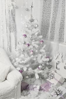 Witte kerstboom met balspeelgoed en geschenkdoos presenteert eronder