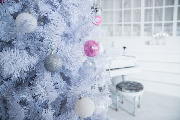 Witte kerstboom versierd met zilveren en roze ornamenten aan de piano