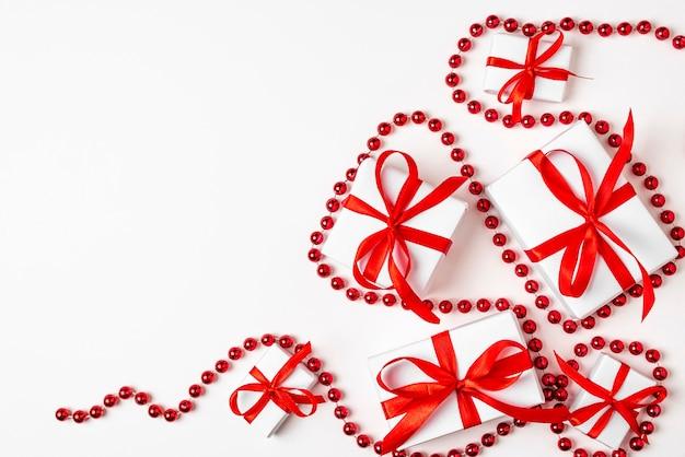 Witte kerstcadeaus met rood lint op witte achtergrond