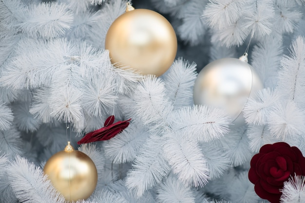 Witte kerstdecoratie met rode ballen en zilveren ballen op kerstboom