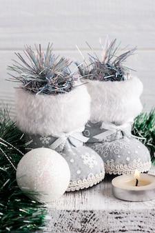 Witte kerstdecoratie met speelgoedlaarzen, bal en aangestoken kaars