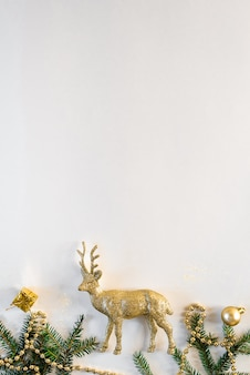 Witte kerstmisachtergrond met kerstboomspeelgoed, gouden herten en spartakken