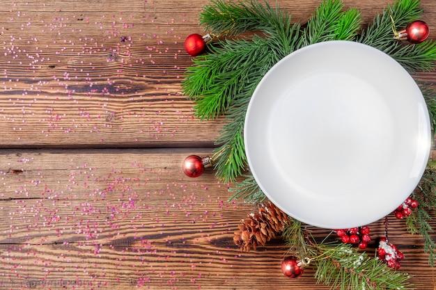 Witte kerstmisplaat met pijnboomtakken met kerstmisdecoratie op houten achtergrond met fonkelingen