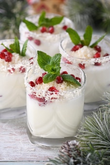 Witte kerstmojito gemaakt van likeur, tequila, kokosmelk met granaatappelpitjes, kokosvlokken en verfrissende munt.