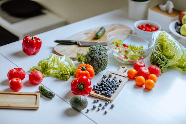 Witte keukentafel met verse groenten zoals paprika, broccoli, kool en bosbessen