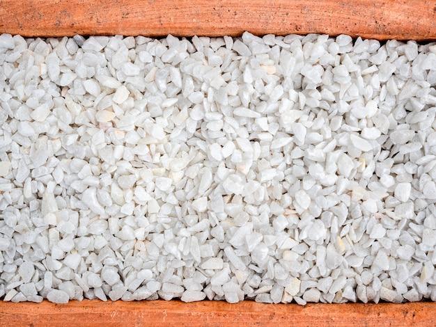 Witte kiezelsteenachtergrond. steen grind textuur in terracotta pot, bovenaanzicht.