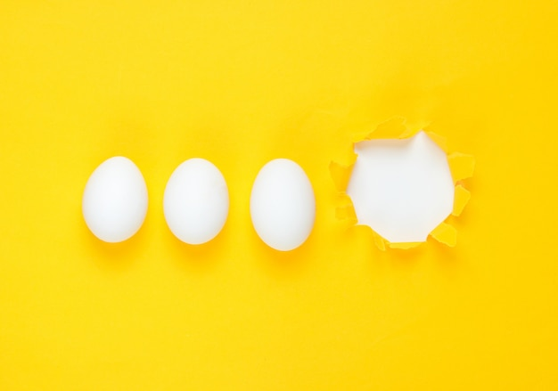 Witte kippeneieren en gescheurd gat geel papier. bovenaanzicht, minimalisme