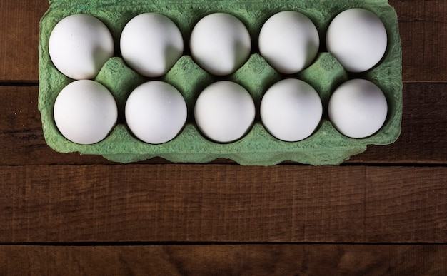 Witte kippeneieren in een groene container op een bruine houten tafel, bovenaanzicht met een kopie van de ruimte.