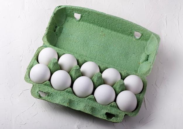 Witte kippeneieren in een groene kartonnen doos, op een witte gestructureerde achtergrond bovenaanzicht.