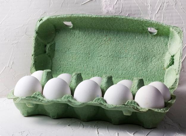 Witte kippeneieren in een groene kartonnen doos, op een witte gestructureerde achtergrond.