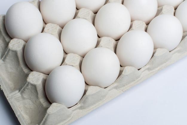 Witte kippeneieren in een kartonnen doos. eieren in een papierlade.