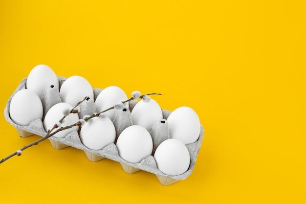 Witte kippeneieren in een open kartonnen doos op een gele achtergrond