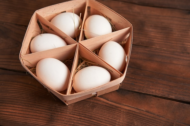 Witte kippeneieren liggen in een ronde houten mand die op een donkere houten tafel staat.