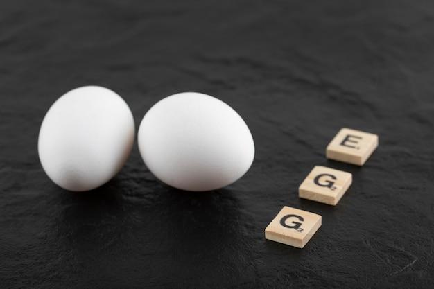 Witte kippeneieren op een zwarte tafel.