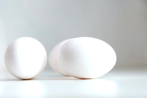Witte kippeneieren op witte achtergrond. ei op tafel, natuurlijke gezonde voeding. creatieve minimalistische achtergrond. concept biologische landbouw en goede voeding. plaats voor een inscriptie of logo