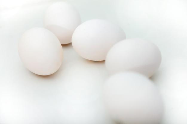 Witte kippeneieren op witte geïsoleerde achtergrond. ei op tafel, natuurlijke gezonde voeding. creatieve minimalistische achtergrond. concept biologische landbouw en goede voeding. plaats voor een inscriptie of logo