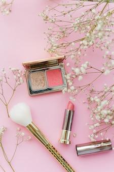 Witte kleine bloemen, cosmetica op een roze oppervlak.