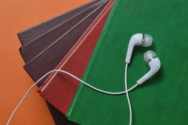 Witte kleine koptelefoon en stapel boeken audioboek concept.