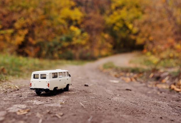 Witte kleine speelgoedauto rijdt op de weg van de herfst gele bomen.