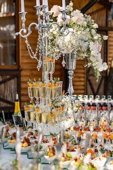 Witte kleur bruiloft tafel versierd met kandelaar. bloemen, kaarsen en glazen met champagne. detailopname.