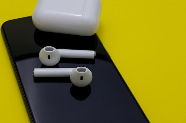 Witte kleur generieke draadloze headset op een zwart oppervlak van een mobiele telefoon met gele achtergrond