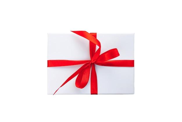 Witte kleur geschenkdoos met rood lint en boog geïsoleerd op wit bovenaanzicht close-up. selectieve zachte focus. tekst kopie ruimte. vakantie aanwezig concept