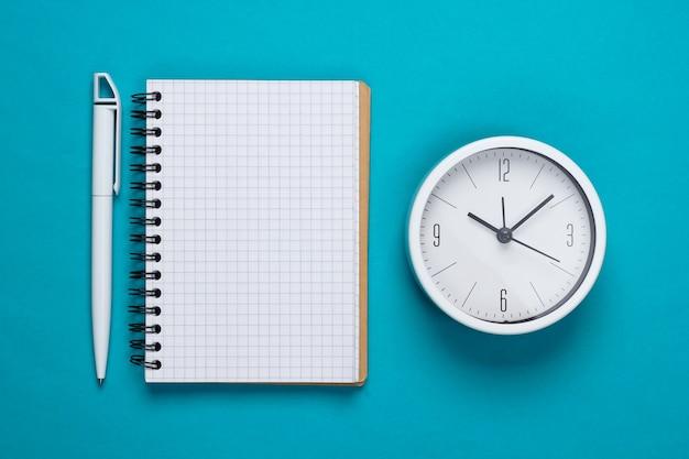 Witte klok en notitieboekje op blauwe achtergrond. minimalistisch studio-opname. bovenaanzicht