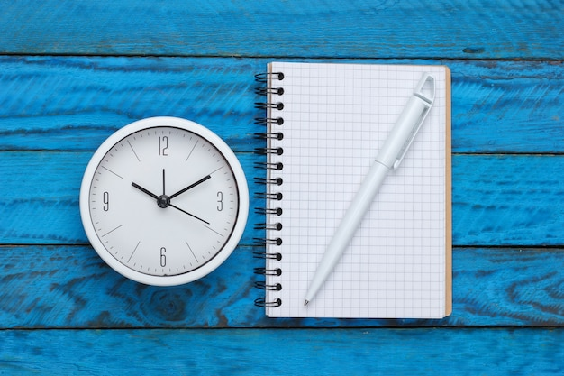 Witte klok en notitieboekje op blauwe houten oppervlak. minimalistisch studio-opname. bovenaanzicht