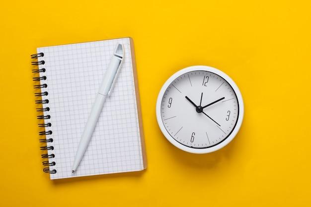 Witte klok en notitieboekje op gele achtergrond. minimalistisch studio-opname. bovenaanzicht