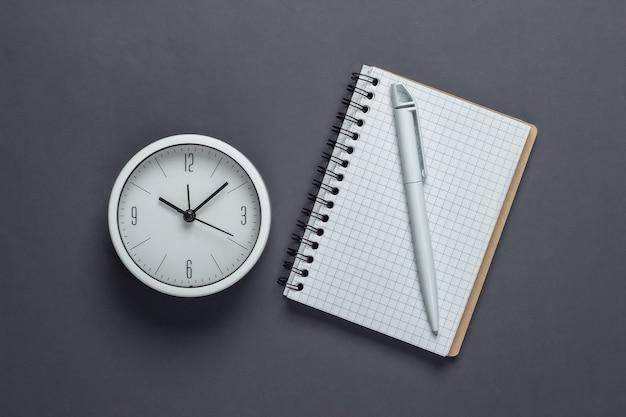Witte klok en notitieboekje op grijs oppervlak. de tijd loopt weg. bovenaanzicht