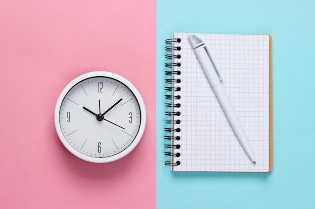 Witte klok en notitieboekje op roze blauwe pastelkleurachtergrond. minimalistisch studio-opname. bovenaanzicht