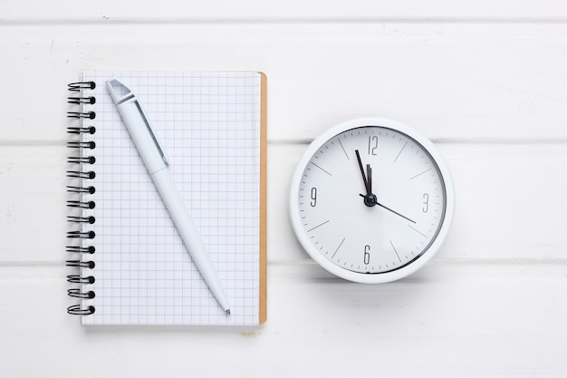 Witte klok en notitieboekje op wit houten oppervlak. minimalistisch studio-opname. bovenaanzicht