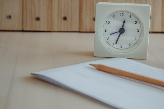 Witte klok gezet dichtbij notebook en potlood