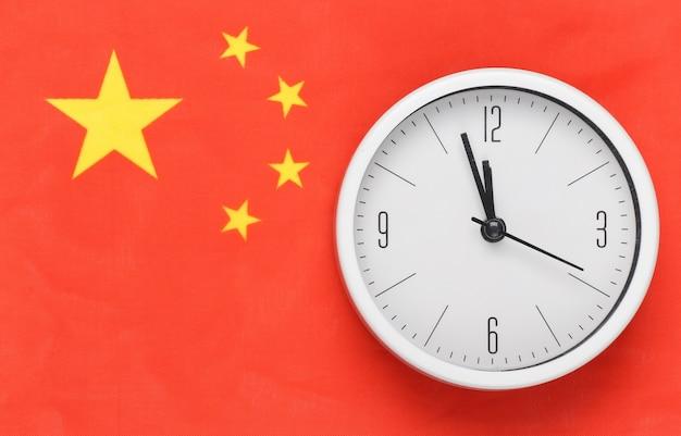 Witte klok op de achtergrond van de vlag van china
