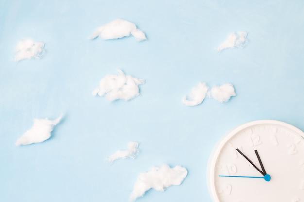 Witte klok op een blauwe achtergrond met wolken van watten, het concept van tijd en afval, plaats kopie