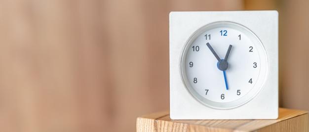 Witte klok op een houten oppervlak. wazig houten muur. kopieer ruimte