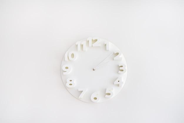 Witte klok op witte muur