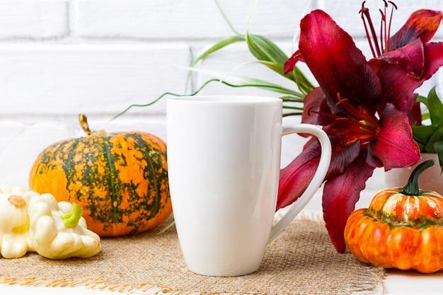 Witte koffie cappuccino mok met pompoen en rode lelie