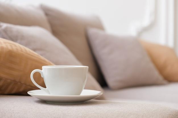 Witte koffiekop en schotel staat op de armleuning van de bank in de woonkamer
