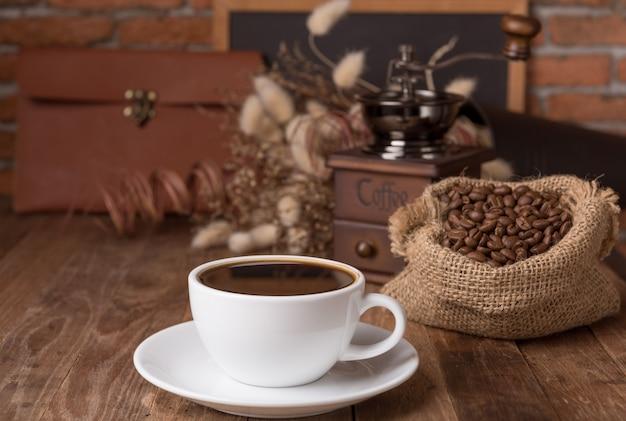 Witte koffiekop, koffiemolen en koffie beens in jutedecor met droge bloem en bord op houten lijst