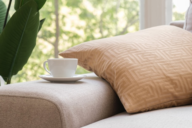 Witte koffiekop op de arm van de bank in de woonkamer concept van een kopje koffie in de ochtend
