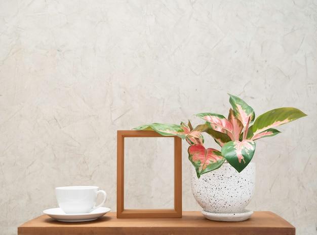 Witte koffiekopje, houten frame en aglaonema kamerplant (chinese evergreen) in moderne bloempotdecoratie op houten tafel met cement muur achtergrond