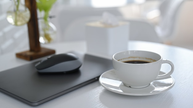 Witte koffiekopje met laptop op witte tafel.