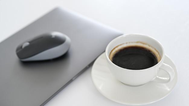 Witte koffiekopje met laptop op witte vloer.