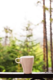Witte koffiekopje op het balkon met wazig uitzicht op de natuur en bos